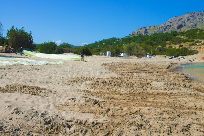 Rhodos, Griekenland, april 2019 Twee mensen vouwen polyethyleen op het strand, voorbereiden het strand in de baai op het seizoen stock foto