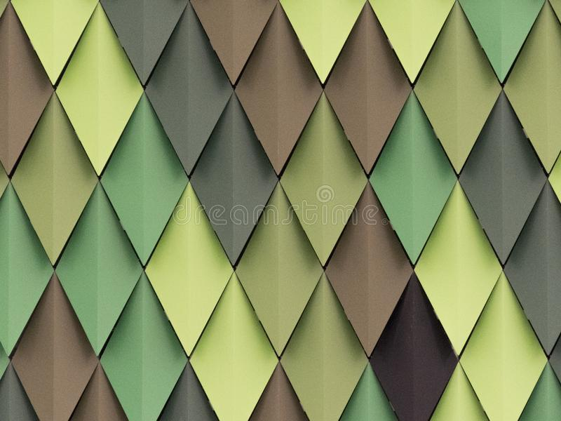 Rhombus in different shades of green and brown in the facade. The facade of the Bilbao Arena sports palace consists of many overlapping diamond shapes of