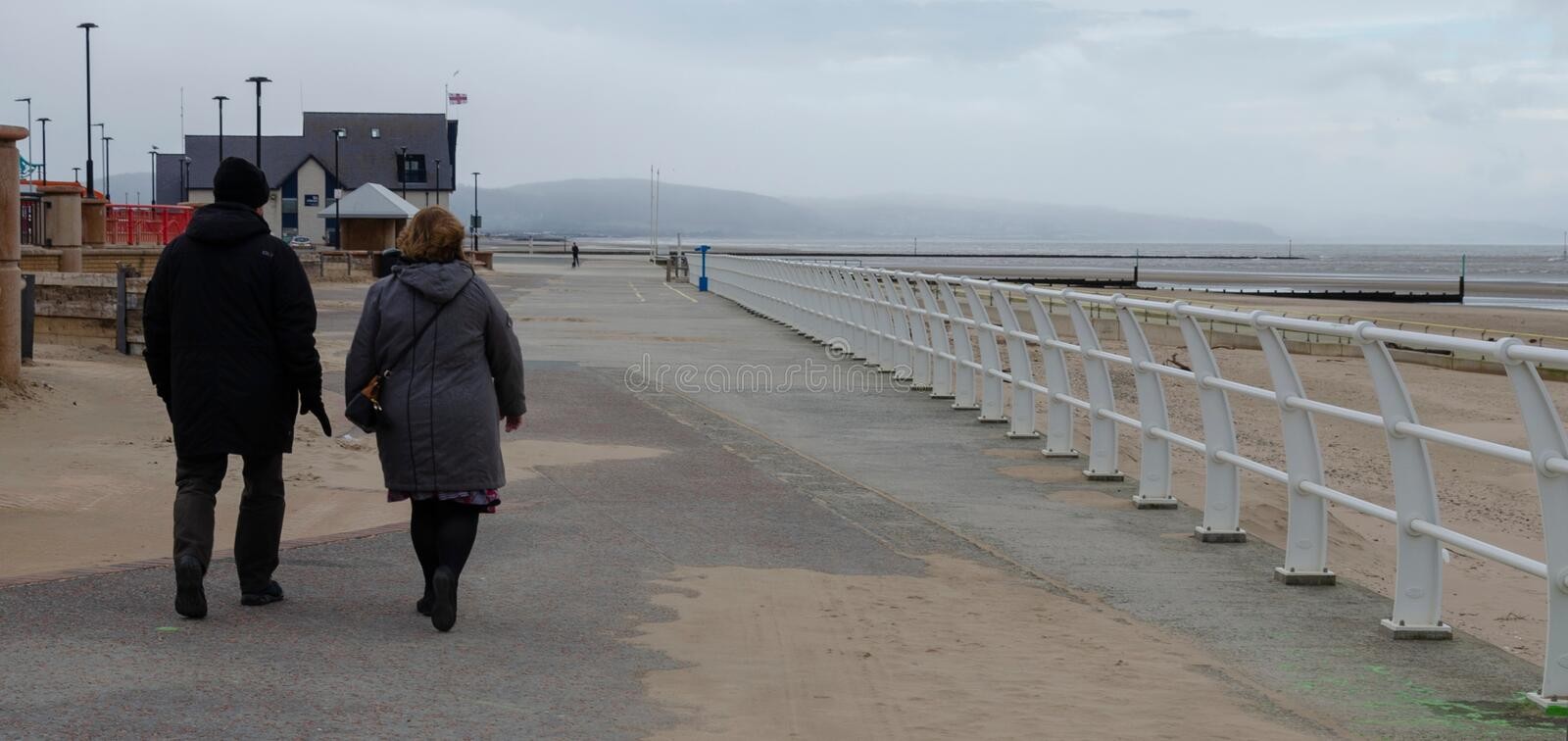 A winters day walk. Rhyl, UK: Jan 7, 2020: A middle aged couple take a walk on the promenade at Rhyl, North Wales on a grey winters day royalty free stock image