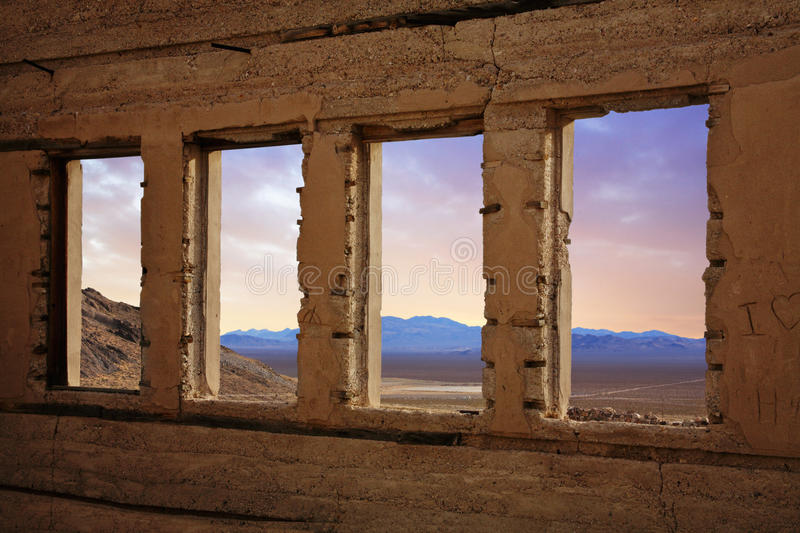 Rhyolite Nevada. Through The Windows Of A Crumbling Structure Overlooking The Amargosa Valley At Rhyolite Nevada, An Abandoned Town Near Death Valley stock photography