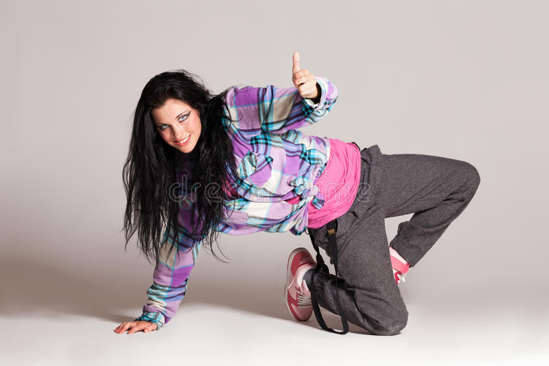 In the rhythm. Girl performing hip-hop dance on gray stock image