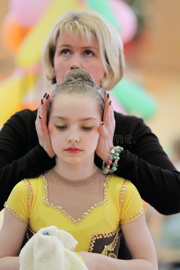 Rhythmic Gymnastics. A young Gymnast awaits her performance at a Rhythmic Gymnastics competition. The Gymnast is Evelyn Trenkenschu , She is accompanied by her stock image