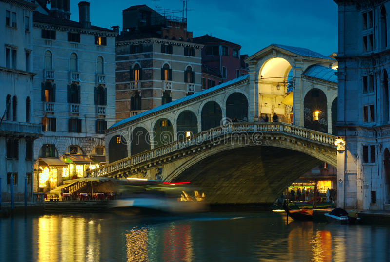 Rialto Bridge at Dusk. A ferry passes under the Rialto Bridge, Venice, Italy, after dusk. Extended exposure has blurred the ferry royalty free stock photos