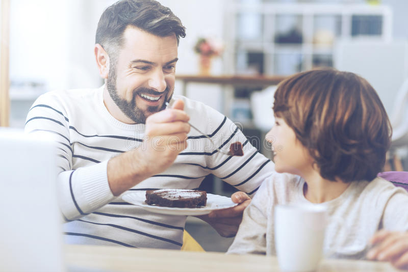 Riant father feeding his son stock image