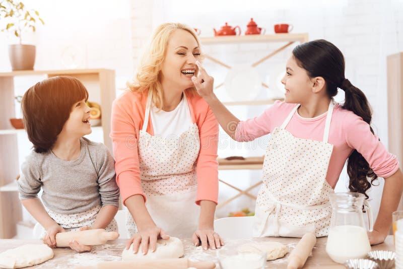 Riant le petit-fils des montres en tant que petite fille enduit le nez de la jeune grand-mère heureuse dans la cuisine de la fari images libres de droits
