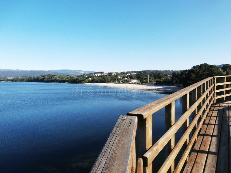 Calm walk along the promenade. Beaches to see, benches to sit. Rianxo is a coastal town with many things to see and many places to go. We walk along the stock photography