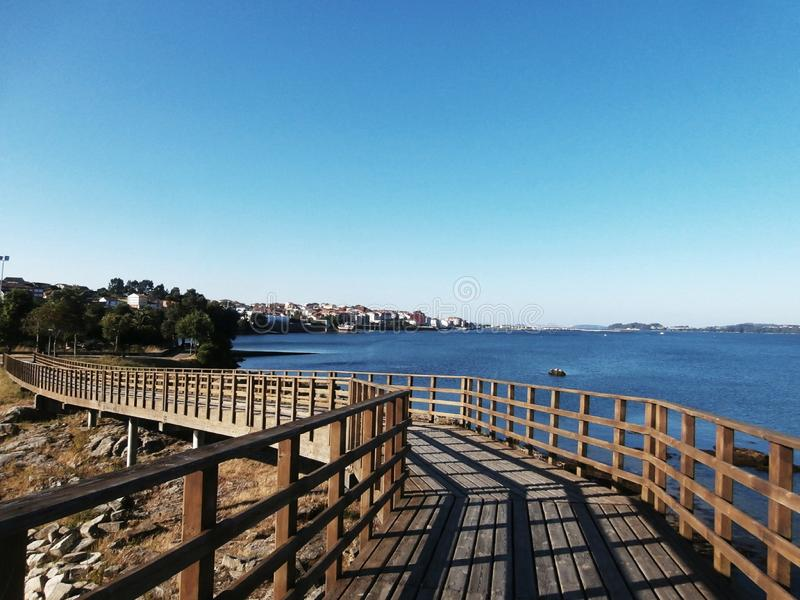 Calm walk along the promenade. Beaches to see, benches to sit. Rianxo is a coastal town with many things to see and many places to go. We walk along the royalty free stock image