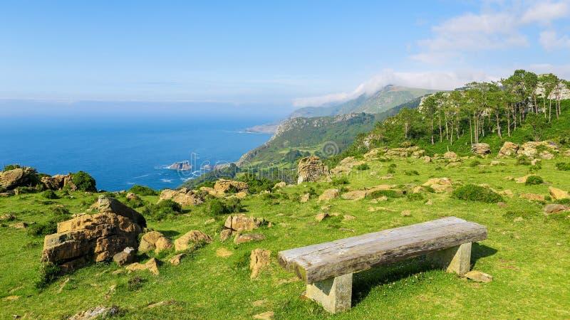 Rias Altas -在一个绿色风景的长木凳 库存图片