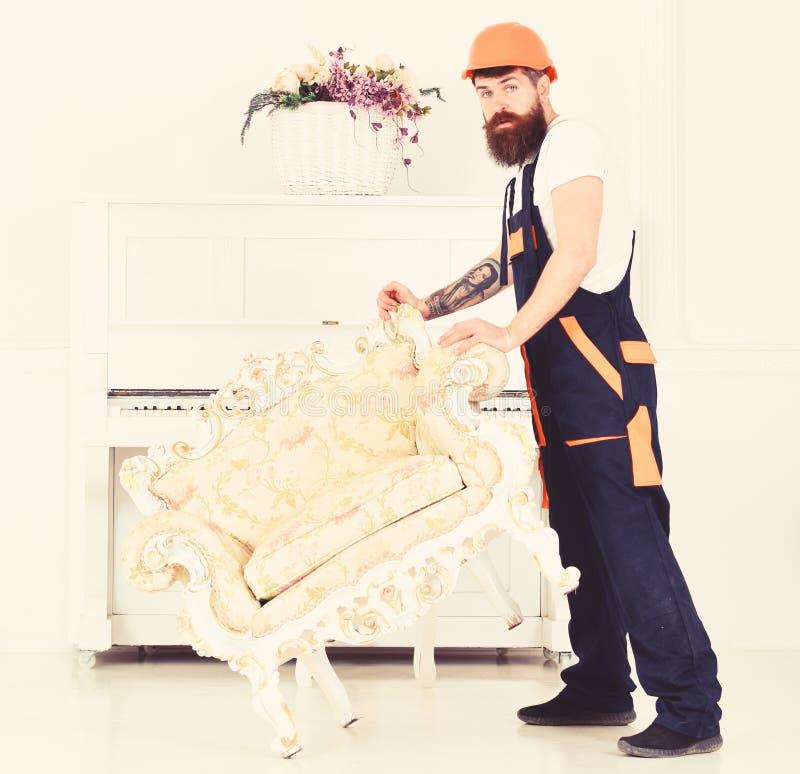 Riassegnazione del concetto Il corriere consegna la mobilia nel caso di va via, la rilocazione Uomo con la barba, lavoratore in c fotografie stock