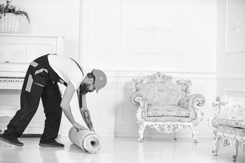 Riassegnazione del concetto Uomo con la barba, lavoratore in camici e tappeto di rotolamento del casco, fondo bianco Il corriere  fotografia stock libera da diritti