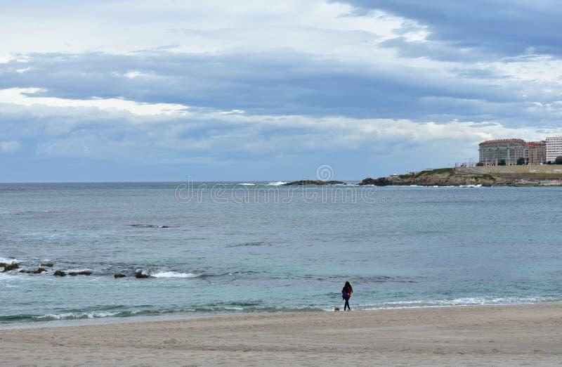 Riazor-Strand mit der Frau, die einen Hund geht Regnerischer Tag, La Coruna, Spanien stockbilder
