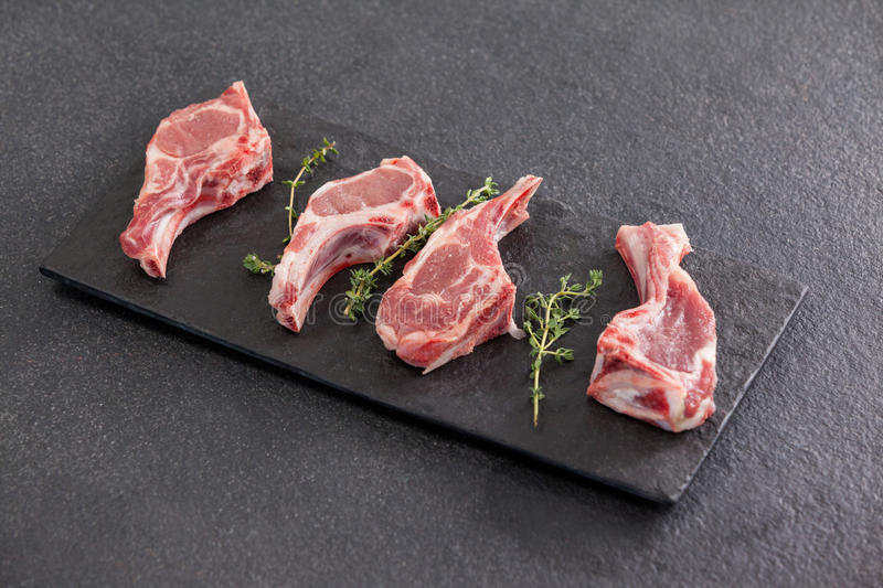 Rib chop and herb on black slate plate. Against black background royalty free stock photo
