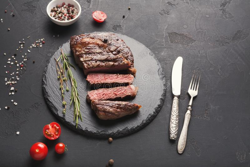 Rib eye steak and spices on black background stock images