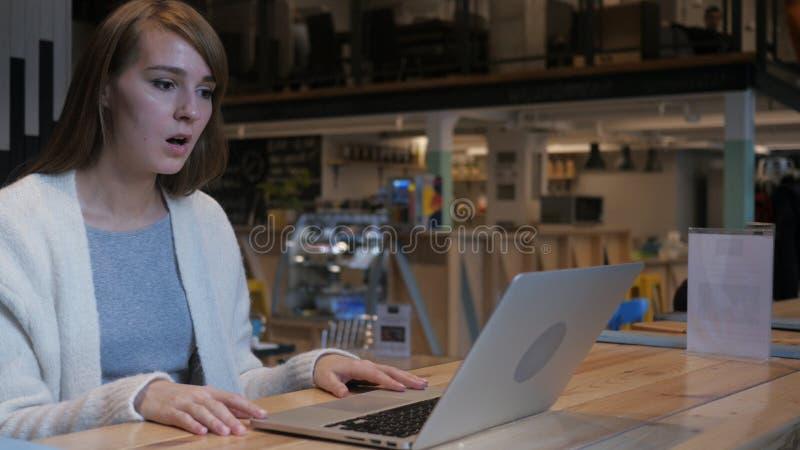 Ribaltamento della giovane donna tramite guasto del progetto, computer portatile immagine stock libera da diritti