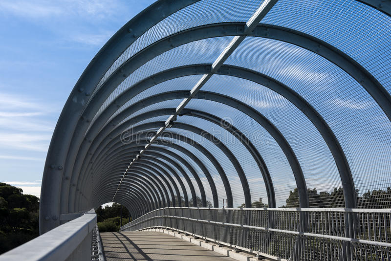 Ribbed pedestrian bridge over highway royalty free stock photography