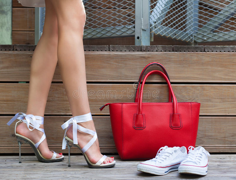 Ribbon Tie Stilleto shoe, sneakers and fashionable big red handbag. Fashionable woman with long beautiful legs standing royalty free stock photography