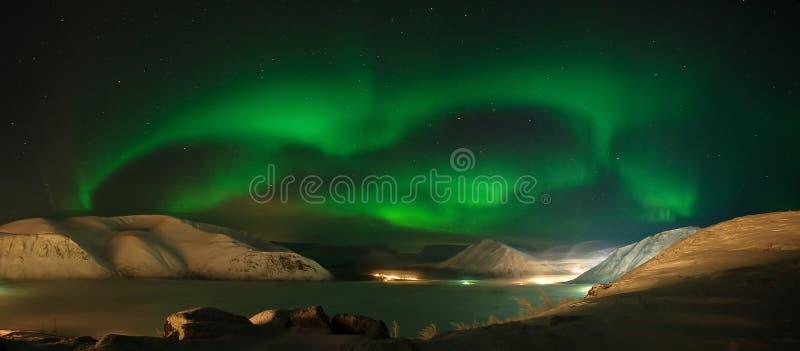 Ribbons of Aurora polaris above mountains stock photo