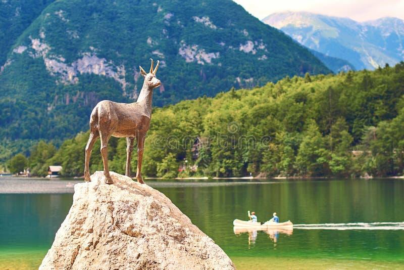 Ribcev Laz, Slovenien - Juli 04, 2017: Brons statyn av Goldhorn Zlatorog hjortar bredvid Bohinj sjön i Triglav royaltyfri fotografi