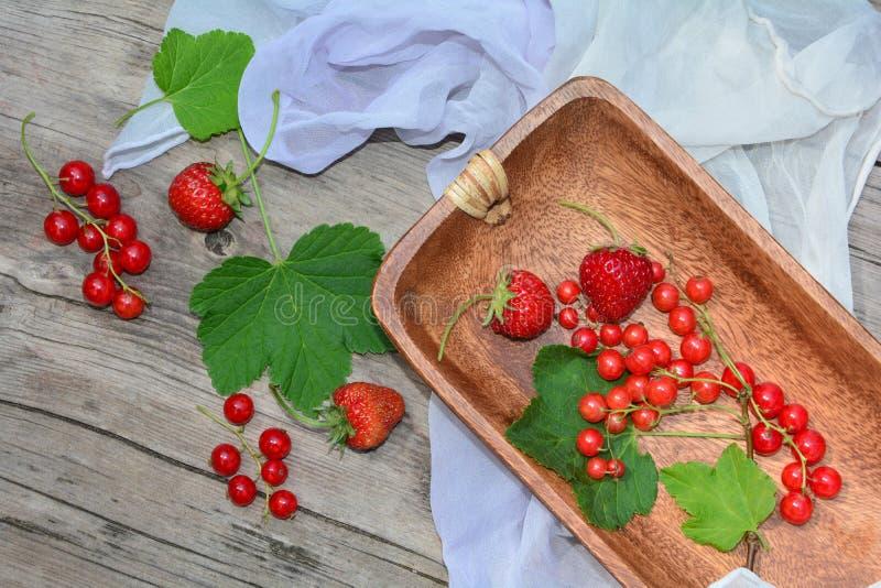 Ribes rosso e fragole, su una tavola rustica con il panno leggero fotografie stock