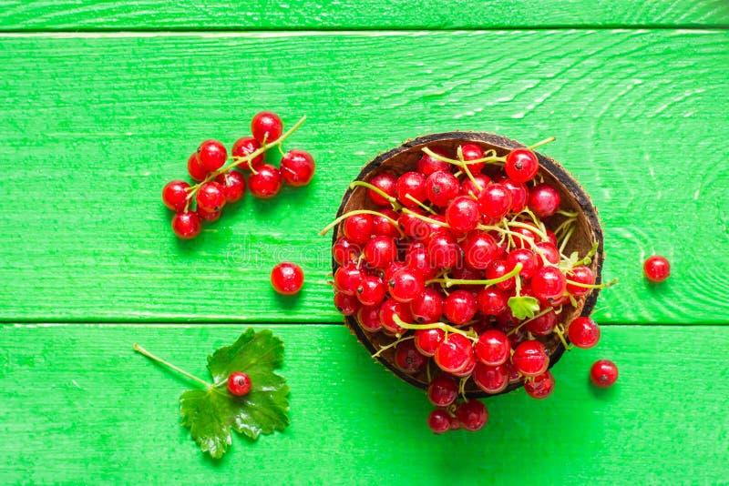 Ribes rosso fresco in una ciotola su una tavola di legno verde Primo piano fotografia stock