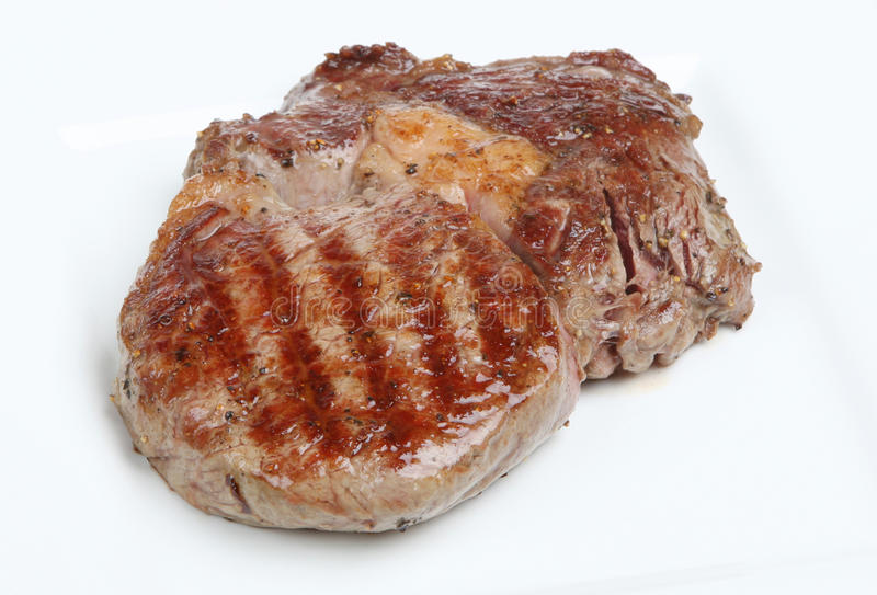Ribeye Steak. Freshly griddled and seasoned ribeye steak resting on a white plate royalty free stock photos