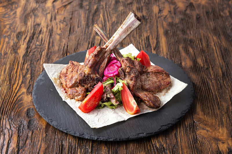 Ribeye steak on the bone. Tomahawk, served with tomatoes and iceberg lettuce on pita on slate board stock photos