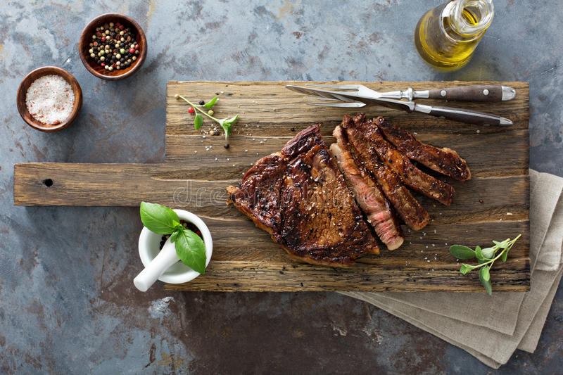 Ribeye steak on a cutting board top view. Ribeye steak seared to medium well on a cutting board top view with herbs, salt and pepper stock photography