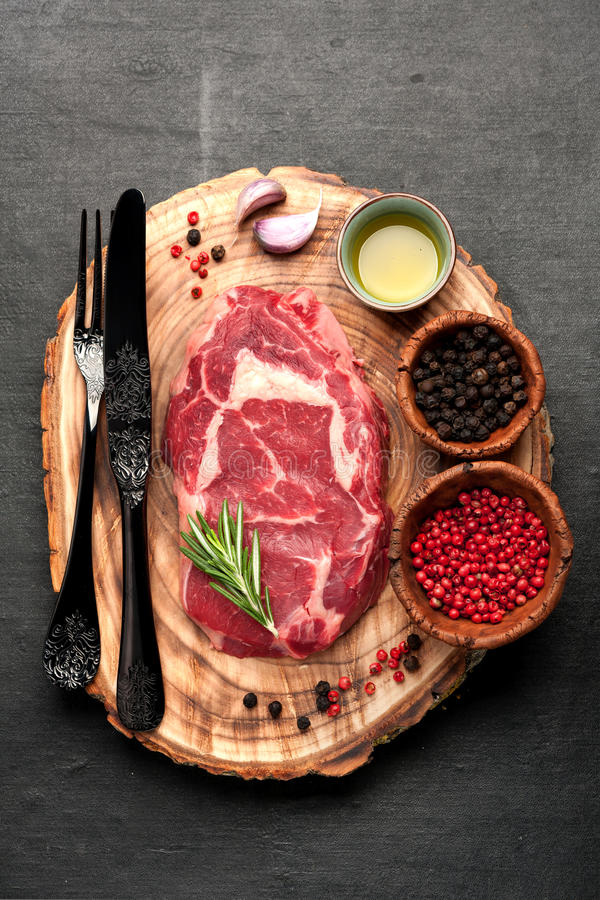 Ribeye steak entrecote. Ribeye steak and spices on a wooden board prepared for roasting royalty free stock photo