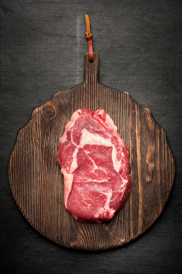 Ribeye steak entrecote. Ribeye steak on a wooden board prepared for roasting. top view stock photos
