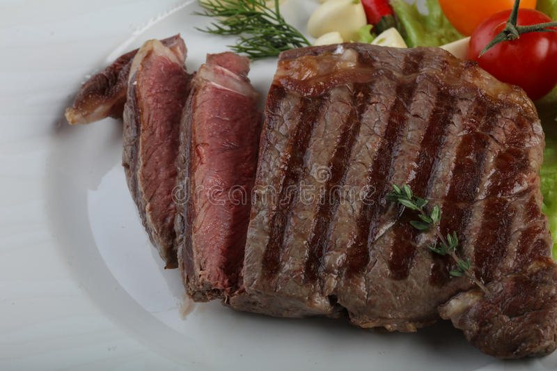 Ribeye steak. Grilled Ribeye steak with pepper, thyme and garlic stock photography