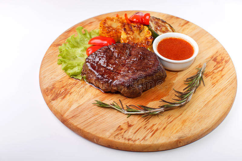 Ribeye steak grilled with rosemary on a wooden. Steak on cutting board on wooden black rustic background stock images