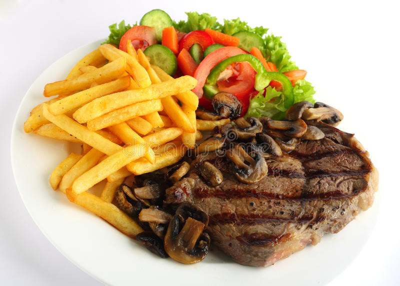 Ribeye steak meal. A grilled ribeye steak served with mushrooms, chips (french fries) and a garden salad of lettuce, cucumber, baby carrot and capsicum royalty free stock photography
