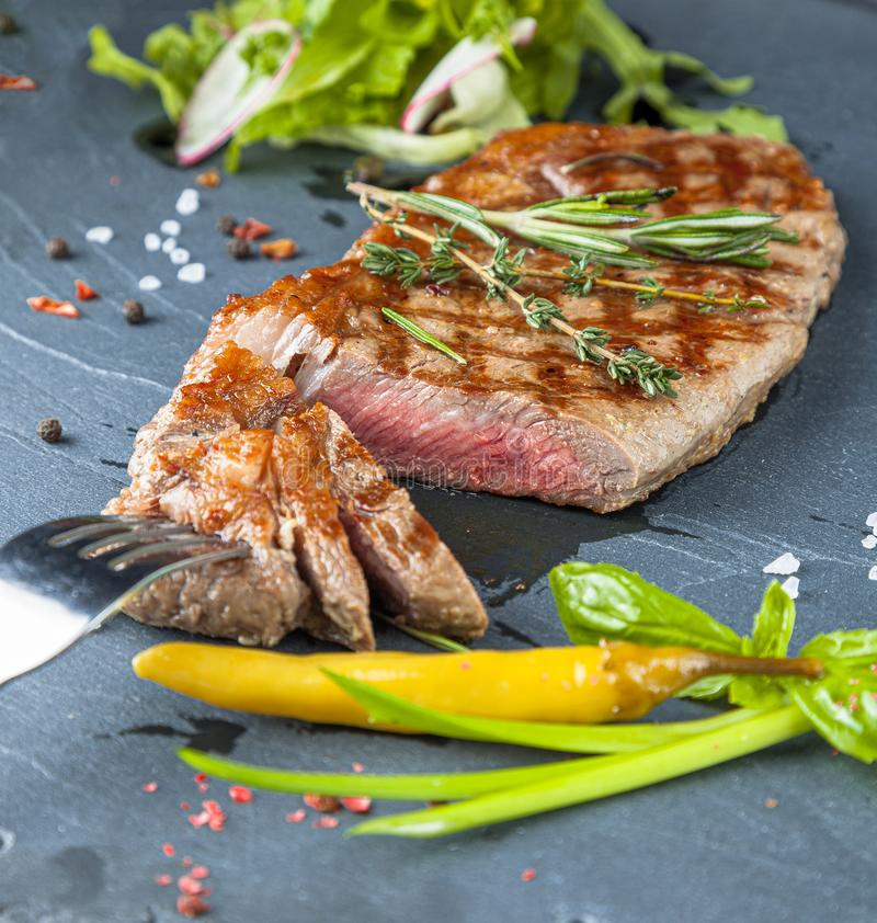 The ribeye steak with sprig of rosemary anh salad on a black stone slab royalty free stock photos
