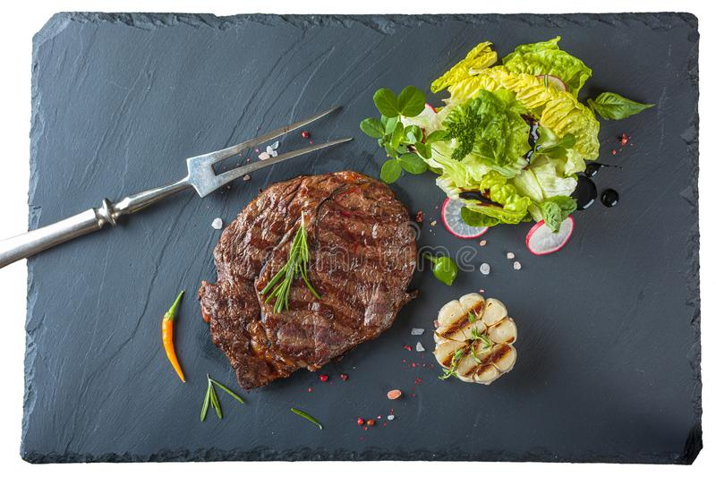 The ribeye steak with sprig of rosemary anh salad on a black stone slab royalty free stock images