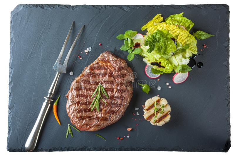 The ribeye steak with sprig of rosemary anh salad on a black stone slab stock image