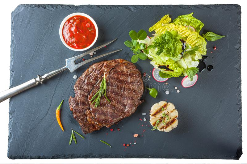 The ribeye steak with sprig of rosemary anh salad on a black stone slab royalty free stock photo