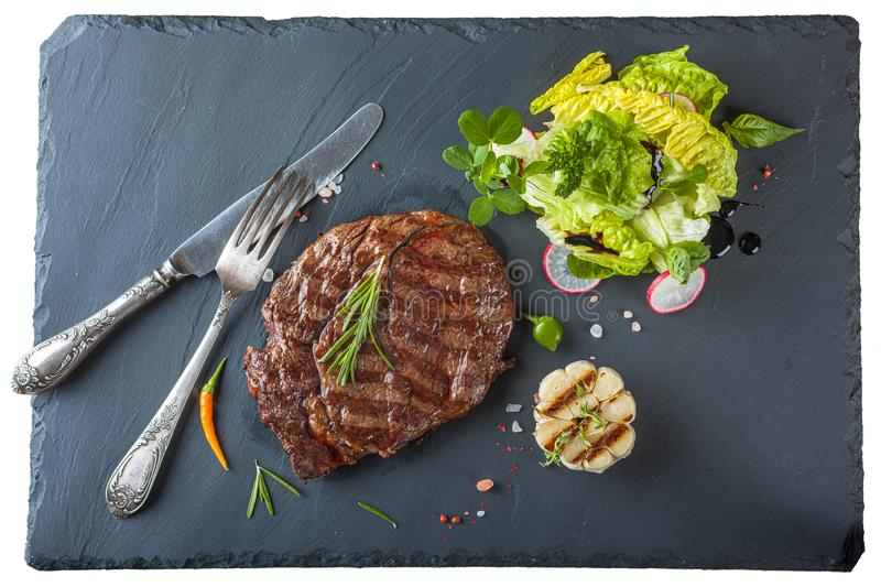 The ribeye steak with sprig of rosemary anh salad on a black stone slab stock photos