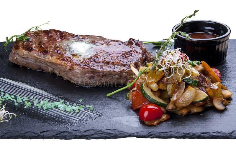 Ribeye steak with vegetables. On white background royalty free stock photo