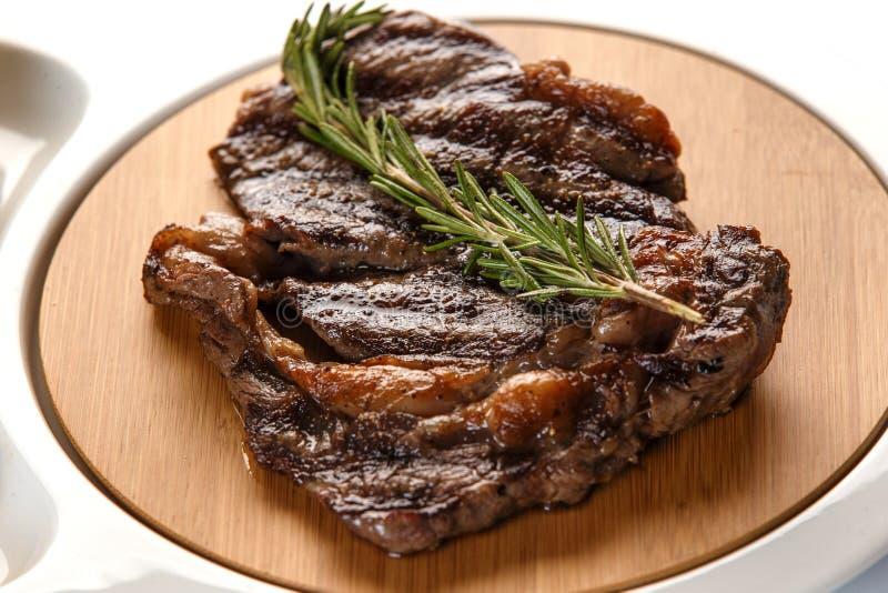 Ribeyelapje vlees dat met een twijg van rozemarijnclose-up wordt verfraaid stock foto