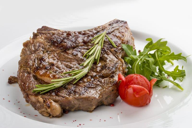 Ribeyelapje vlees met rozemarijn Op een witte plaat royalty-vrije stock foto