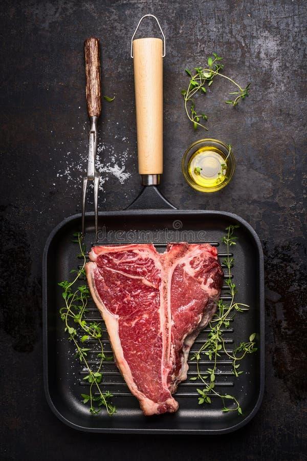 Riblapje vlees bij het braden van grillpan met vlees vork, olie en het kruiden op donkere rustieke achtergrond royalty-vrije stock afbeelding