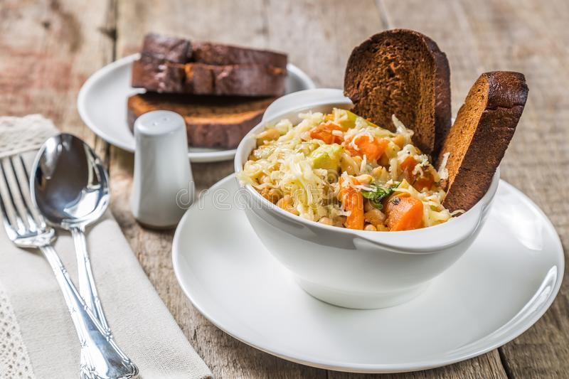 Ribollita soup with beans, vegetables, cheese and croutons. A typical Tuscan dish. Ribollita soup with beans, vegetables, cheese and croutons on an old wooden stock image