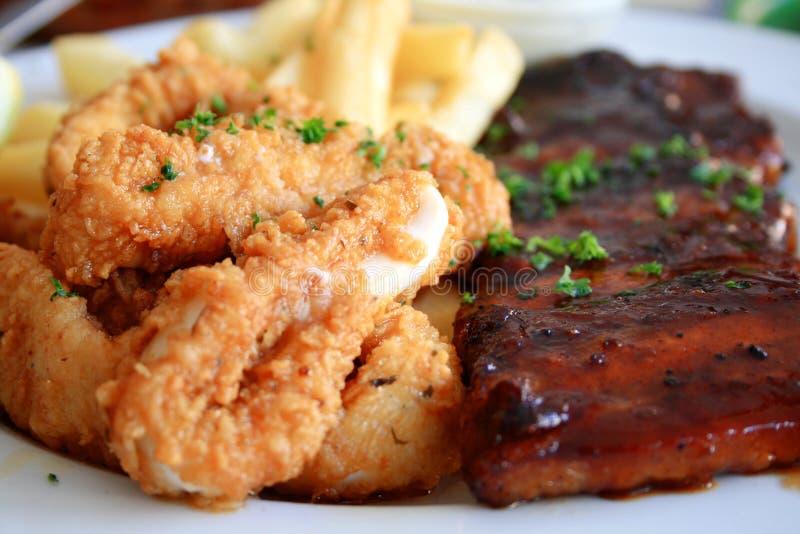 Ribs and calamari. Deep fried calamari and juicy pork ribs on a plate royalty free stock photo