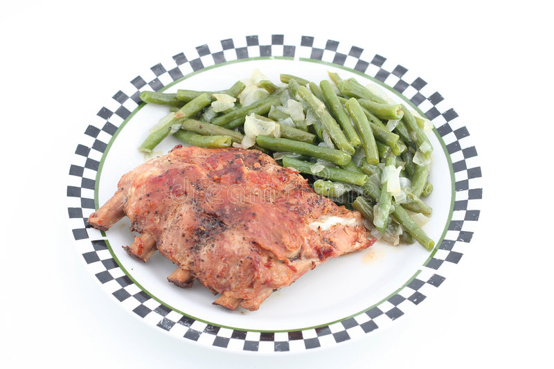 Ribs with green beans. Baked ribs with green beans on a plate royalty free stock image
