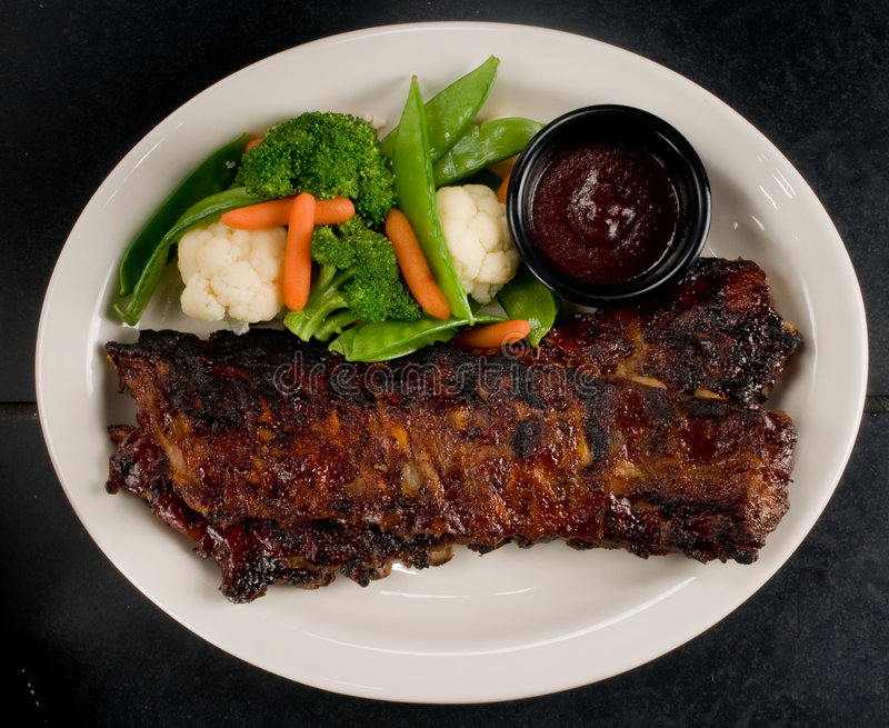 Ribs with steamed vegetables royalty free stock image