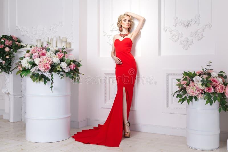 Ricamente senhora com o vestido longo vermelho, a joia e cabelo ondulado louro, p imagens de stock