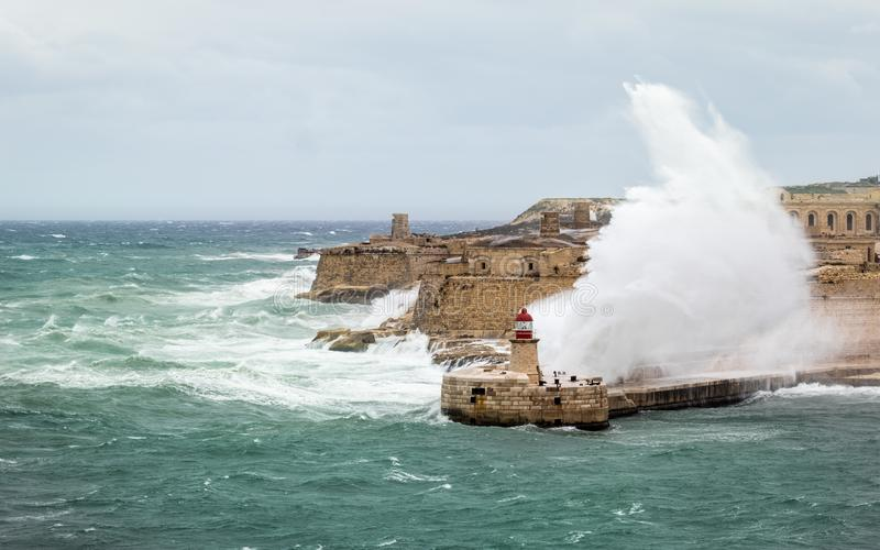 Ricasoli East Breakwater and Lighthouse withstand raw sea and high waves. Giant waves punshing on the Breakwater. Stormy day and raw sea near the grand harbour royalty free stock image