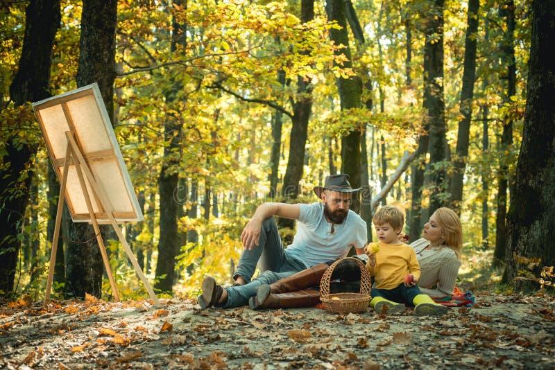 Ricavando dalla vita Artista del pittore con la famiglia che si rilassa nella pittura della foresta in natura Nuova immagine di i fotografie stock libere da diritti