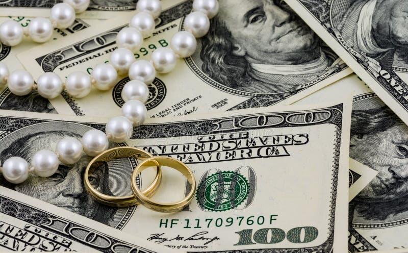 Ricchezza, dollari americani, anelli dorati e perle reali fotografie stock libere da diritti