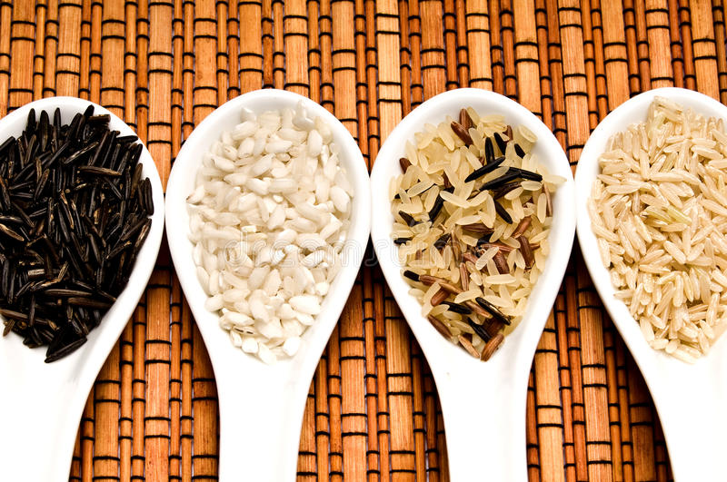 Rice. Various kinds of rice - jasmine rice, white rice, black rice, wild rice in white spoons over bamboo background